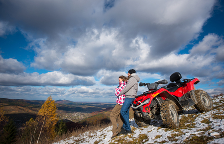 Man hugging a woman near the red quad bike on a mountain slope under the blue sky with cumulus clouds at background of mighty mountains and village in the valley