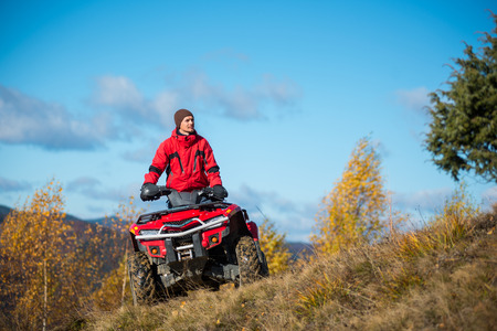 Bottom view. A man on the red ATV quad bike against blue sky in the autumn landscape nature. Copy space Stock Photo