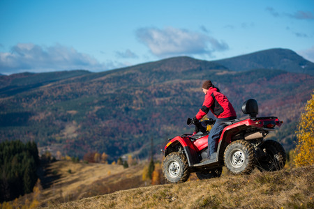 Male on an ATV riding down the hilly road on a background of mountains, forest and blue sky. The concept of an active holiday in the mountains