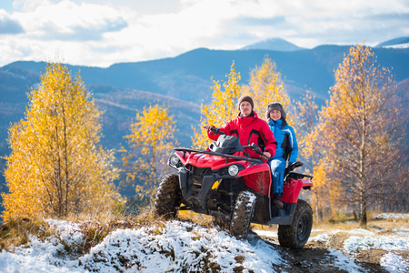Couple on snow-covered road driving a quad bike on a sunny autumn day on the background of mountains and trees with yellow leaves