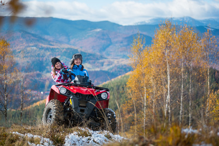 Happy females ATV driver in winter clothing on snowy hills on the background of mighty mountains and trees with yellow leaves. Girl is showing something in distance to her friend. Sunny autumn day Stock Photo