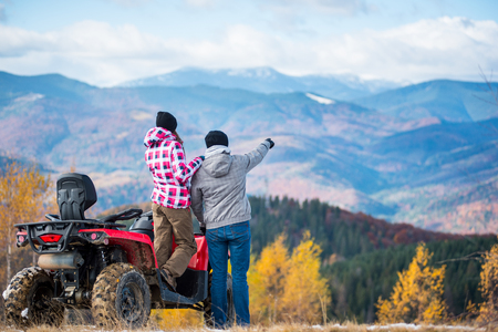 Rear view of young couple near red quad bike. Guy is showing something in distance to her girlfriend. Blurred autumn landscape mighty mountains and forests on background Stock Photo