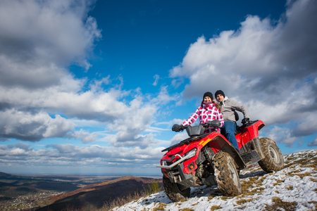 Smiling couple in winter clothes on a red quad bike on a mountain slope under the blue cloudy sky on background of mountains and the town in the valley