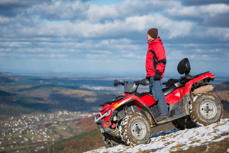 Man in winter clothes standing on a red quad bike on a mountain slope under the blue cloudy sky and looks into the distance on a blurred background of mountains and the city in the valley