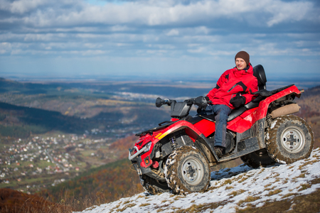 Man in winter clothes resting on a red atv bike on a snowy mountain top, looking to the camera on a blurred background of mountains and the town in the valley with copy space