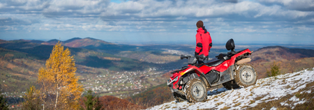Panorama picture. Off-road vehicle and man near him on a snowy mountain top under the blue cloudy sky on a blurred background of autumn mountains and the town in the valley with copy space Standard-Bild