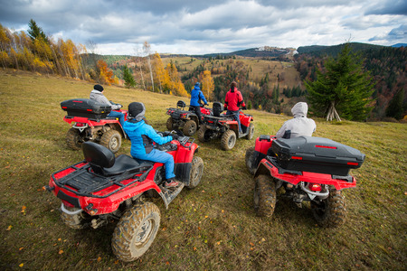 Rear view group of five person riding quad bikes on hill and enjoying beautiful autumn scenery of colorful trees in the forest and mountainous areas Stock Photo