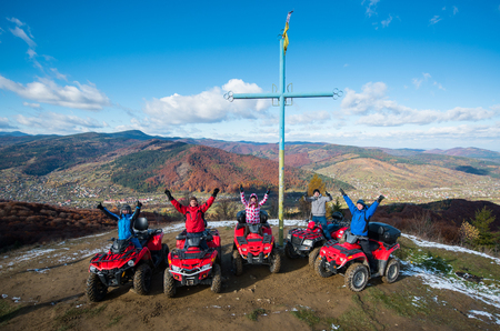 Group of people with raised hands up on red quad bikes near cross with a symbol of Ukraine on top of the mountain on the background of mountains and blue sky in winter at sunny day