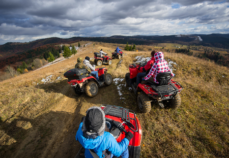 Top view of a group of people riding a off-road vehicles on a mountain road under a sky with clouds in autumn