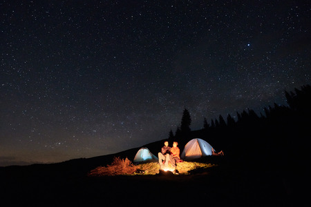 Night camping. Couple tourists sitting at a campfire near two illuminated tents under night starry sky. Long exposure