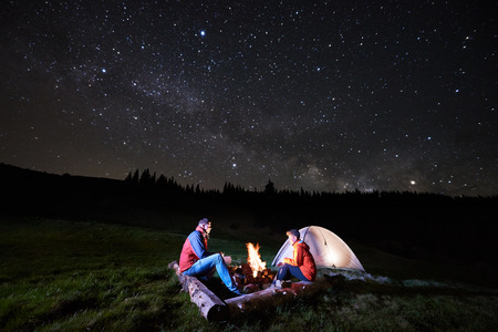 Night camping. Man and woman tourists sitting at a campfire near illuminated tent under night starry sky. Astrophotography