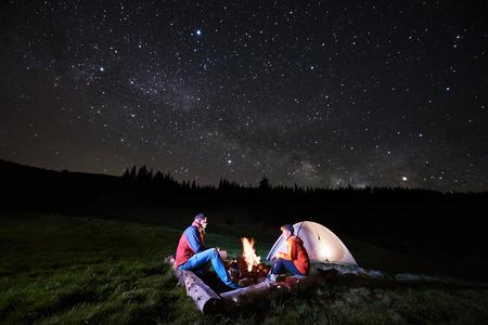 Camping de noche. Hombre y mujer turistas sentados en una fogata cerca de tienda iluminada bajo cielo estrellado de noche. Astrofotografía Foto de archivo - 80723572