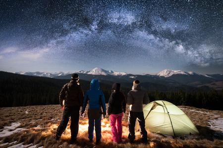 Silhouet van vier mensen die naast kamp en tent zich onder het mooie hoogtepunt van de nachthemel van sterren en melkachtige manier verenigen. Op de met sneeuw bedekte bergen op de achtergrond. Achteraanzicht. Lange blootstelling