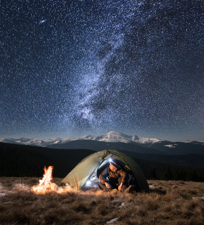 Male tourist have a rest in his camping in the mountains at night. Man with a headlamp sitting near campfire and tent under beautiful night sky full of stars and milky way, and enjoying night scene Stok Fotoğraf