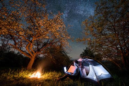 Turista femenino que usa su computadora portátil en acampar en la noche. Mujer sentada cerca de fogata y carpa debajo de árboles y hermoso cielo nocturno lleno de estrellas y vía láctea