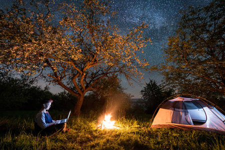 Female tourist using her laptop in the camping at night. Woman sitting near campfire and tent under trees and beautiful night sky full of stars and milky way