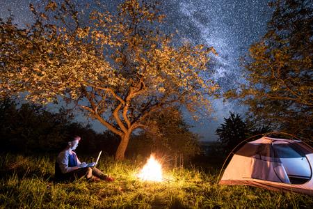 Turista femenino que usa su computadora portátil con el receptor de cabeza en acampar en la noche. Mujer sentada cerca de fogata y carpa debajo de árboles y hermoso cielo nocturno lleno de estrellas y vía láctea Foto de archivo