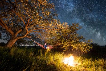 Turista femenina utilizando su computadora portátil en el camping por la noche. Mujer sentada en la hamaca cerca de fogata bajo los árboles y hermoso cielo nocturno lleno de estrellas y vía láctea. En la ciudad luminosa de fondo Foto de archivo