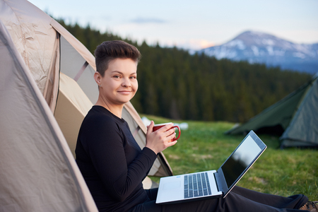 Shot of a happy young woman smiling to the camera holding her drink relaxing outdoors while camping sitting near the tent with her laptop Stock Photo