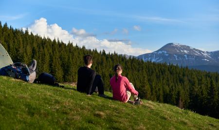 Rearview shot of two female hikers sitting near their tent and backpacks enjoying beautiful mountains view copyspace lifestyle activity sport health friendship travelling evening
