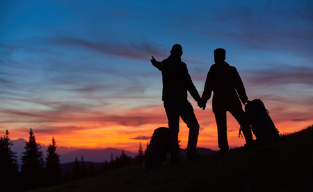 Silhouettes of loving couple enjoying sunset while hiking mountains together copyspace love people affection romance nature landscape travelling sky