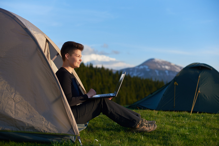Young woman enjoying sunrise in the mountains sitting in her tent working on the laptop copyspace camp site travelling mobility technology internet online studying tourism