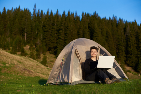 Happy young female admiring the view while sitting in her tent in the mountains and working on a laptop copyspace technology connectivity mobility wireless connection project.
