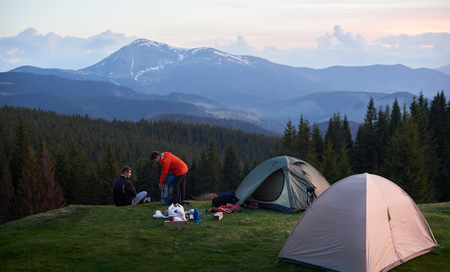 Male and female tourists in the camping near two tents while hiking together with their backpacks. On the background beautiful forests and mountains. Carpathians mountains, Ukraine