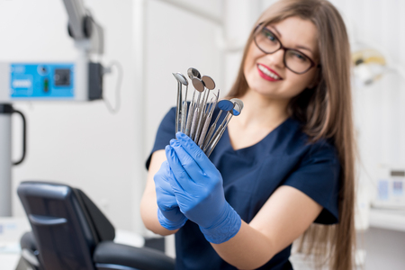 Smiling female dentist with blue gloves holding tools - dental mirrors and dental probes at the dental office. Close-up, selective focus on tools. Dentistry Stock Photo