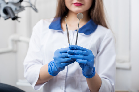 Female dentist with blue gloves holding tools - dental mirror and dental probe at the dental office. Close-up, selective focus on tools. Dentistry