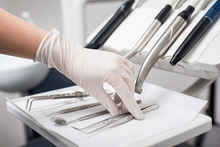 Dentist with gloved hand is picking dental tweezers in dental office. Close up, selective focus. Dentistry