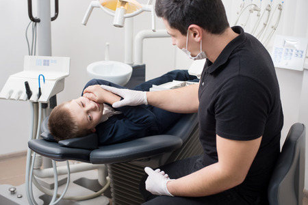 Boy patient with toothache complaining to pediatric dentist at dental clinic office. Medicine, dentistry and health care concept. Dental equipment