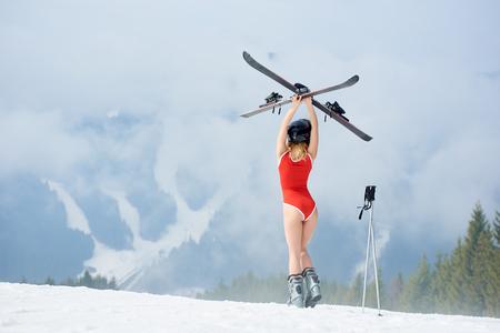 、スキーリゾートで雪の斜面に立って、頭の上にスキーを持って、ボディスとヘルメットを身に着けているセクシーな女性のスキーヤーのバックビ
