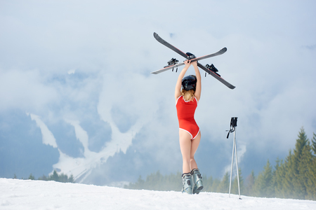 Back view of sexy woman skier wearing bodice and helmet, holding skis above head, standing on the snowy slope at ski resort. Mountains, forests, ski slopes and fog on the background Archivio Fotografico