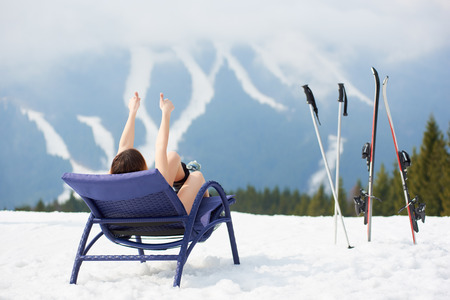 chairs: Back view of woman skier showing thumbs up, enjoying on a blue deck chair near skis and poles at ski resort. Mountains, ski slopes and forest on the background. Ski season and winter sports concept