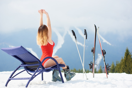 Sporty young woman skier wearing red swimsuit, enjoying on a blue deck chair near skis and poles at ski resort. Mountains, ski slopes and forest on the background. Ski season and winter sports concept
