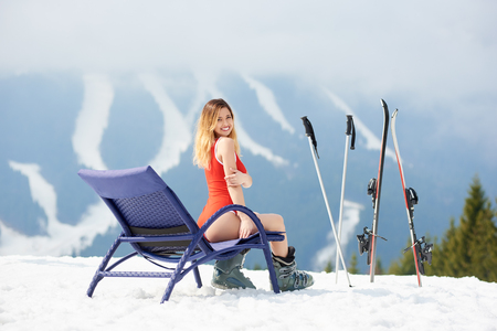Beautiful woman skier wearing red bodice, sitting on a blue deck chair near skis and poles at ski resort. Copyspace recreation travelling extreme adrenaline ski season and winter sports concept