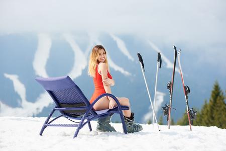 Esquiador de la mujer hermosa que lleva el corpiño rojo, sentándose en una silla de cubierta azul cerca de los esquís y de los polos en la estación de esquí. Copyspace recreación viajando extrema adrenalina estación de esquí y el concepto de deportes de invierno