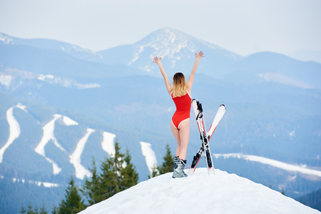 Back view of happy female skier wearing red bodice, enjoying with skis on the top of the hill at ski resort. Mountains, forests, ski slopes on the background. Ski season and winter sports concept Imagens