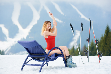 chairs: Smiling woman skier wearing red bodice, posing on a blue deck chair near skis and poles at ski resort. Mountains and ski slopes on the background. Ski season and winter sports concept