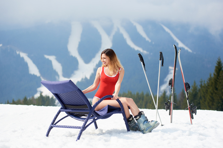 Attractive woman skier wearing red swimsuit, sitting on a blue deck chair near skis and poles at winter ski resort on the top of the hill. Mountains, ski slopes and forest on the background Stock Photo