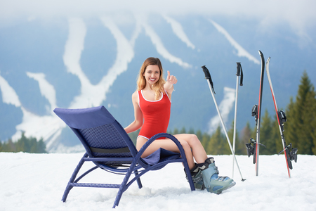 chairs: Happy woman skier wearing red bodice, showing thumbs up, having a rest on a blue deck chair near skis and poles at ski resort. Mountains, ski slopes and forest on the background