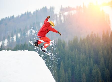 남성 스노 freerider 스노우 보드와 함께 눈 덮인 언덕 꼭대기에서 점프. 스키와 스노우 보드 개념 스톡 콘텐츠