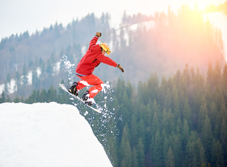 Male snowboarder freerider jumping from the top of the snowy hill with snowboard. Skiing and snowboarding concept Banco de Imagens - 89494475