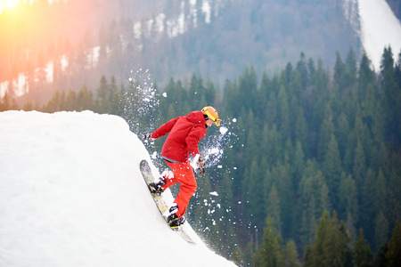 Male snowboarder in a red suit riding from the top of the snowy slope with snowboard. Skiing and snowboarding concept Stock Photo