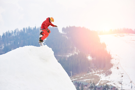 Man snowboarder jumping from the top of the snowy hill with snowboard in the evening at sunset. Ski slope, ski-lift, forests and mountains on the background. Skiing and snowboarding concept