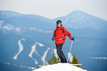 Male skier standing on the top of the slope at winter ski resort. Mountains, forests and ski slopes on the background. copyspace recreation travelling tourism vacation extreme adrenaline Stock Photo