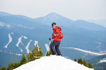 Man skier standing on the top of the slope at ski resort Bukovel. Mountains, forests and ski slopes on the background recreation active sport seasonal resort sportspeople adrenaline extreme concept Stock Photo