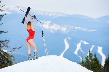Back view of sporty girl skier wearing bodice, holding skis above head, standing on the top of slope at ski resort. Mountains and ski slopes on the background. Ski season and winter sports concept