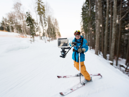 Skier man taking selfie with stick over forest on the winter resort. Focus on his camera, blurred background Stock Photo